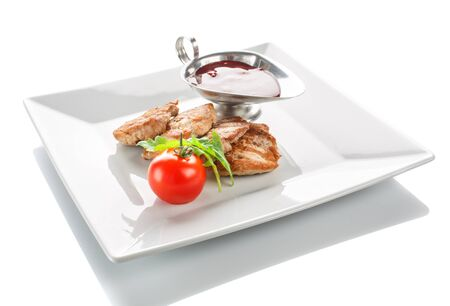 A grilled serving of succulent tender peppered steak garnished with tomato and fresh herbs and sauce on white background