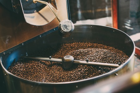 Fresh Coffee Beans - Freshly roasted spinning cooler professional machine. Foto de archivo
