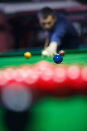 young man lines up his shot as he breaks the balls for  start  game of billiards Banque d'images