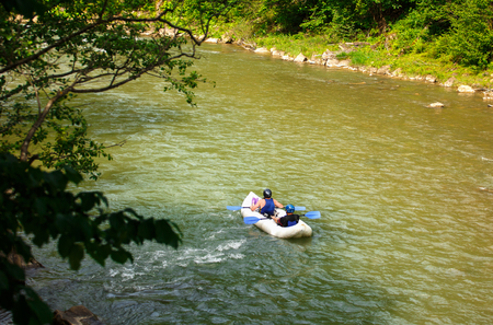 two people floating in a canoe with oars on a mountain river