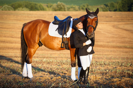 horse, animal, active recreation and lfestyle concept - Happy Woman with her Horse - Beautiful young horsewoman next to her horse. equestrian. Banco de Imagens