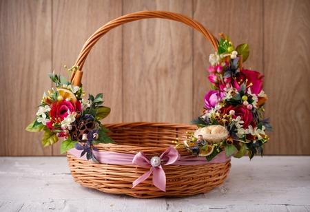 Designer Korb ist mit Blumen geschmückt. Weidenkorb für das Feiern von Ostern und von anderen Feiertagen.