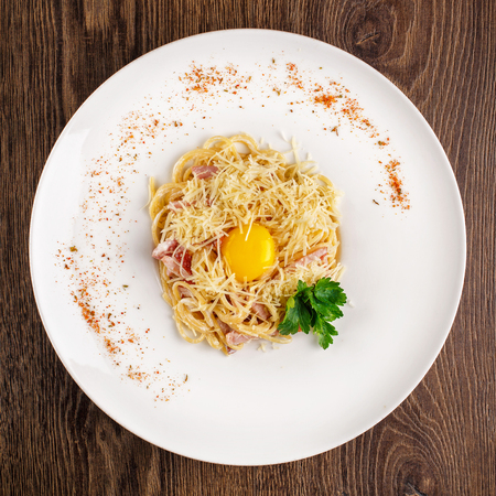Pasta Carbonara. Spaghetti with bacon, parsel and parmesan cheese. Pasta Carbonara on white plate with parmesan on wooden background. Italian food concept. Top view.
