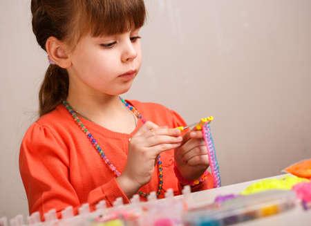 Girl weaves jewelry bracelet gum, gum weaving, hobby concept