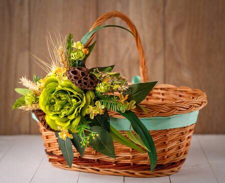 Schöner Korb ist mit einer Blumenanordnung für die Feier des Ostern dekoriert
