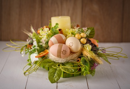 Decorated Easter candlestick with painted eggs with flowers on wooden boards