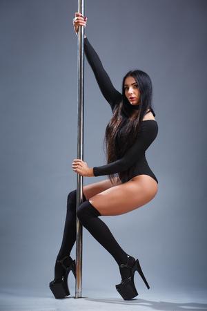 Sexy Brünette. Der Master Pool Dance zeigt sein Können. Fit Mädchen in der Nähe des Rohres