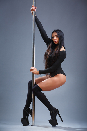 Sexy Brunette. The master pool dance shows his skill. Fit girl near the pipe Stock Photo