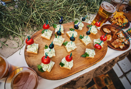 Delicious snacks for beer. Fresh canapes with tomatoes, olives, greens on white bread on a board, along with a mug of beer.