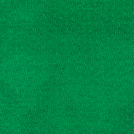 Fabric of green color for warm autumn dress or skirt.On the fabric is a picture in the form of black rhombus