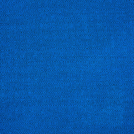 Fabric of blue color for warm autumn dress or skirt.On the fabric is a picture in the form of black rhombus Stock Photo