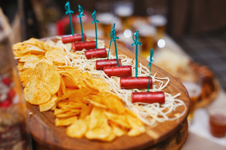Delicious snacks for beer. A board with hunting sausages and cheese. Stock Photo