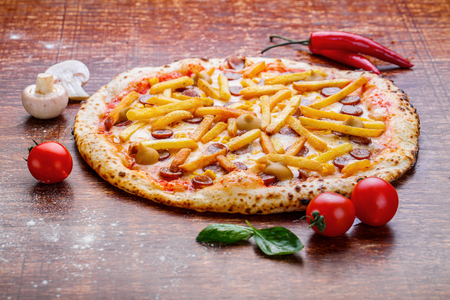 Pizza with french fries and sausage.Appetizing pizza with sausage, cheese and potatoes
