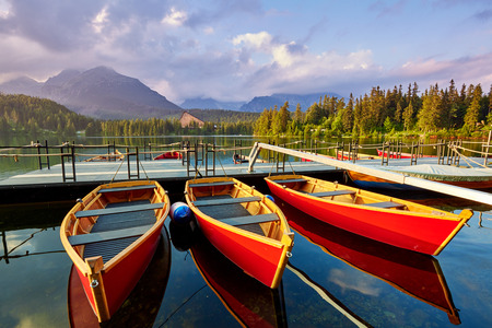 Red boats near the pier on a mountain lake in the National Park. High Tatras Slovakia Europe Stock Photo