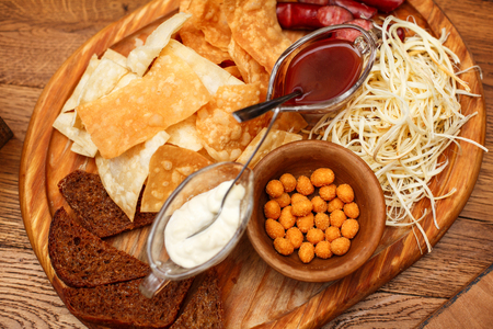 Tasty snacks for beer. Hot hunting sausages, cheese, chips, white and red sauce on the board.