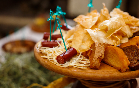 Delicious snacks for beer. A board with hunting sausages, cheese, chips and rye bread