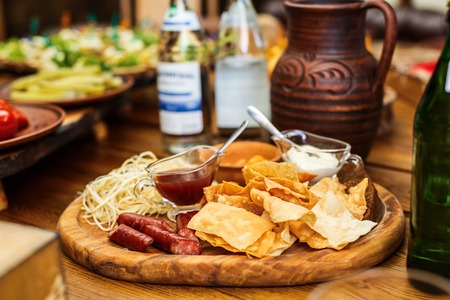 Delicious snacks for beer. Hot hunting sausages on the cheese next to the chips and sauces on the board. Stock Photo