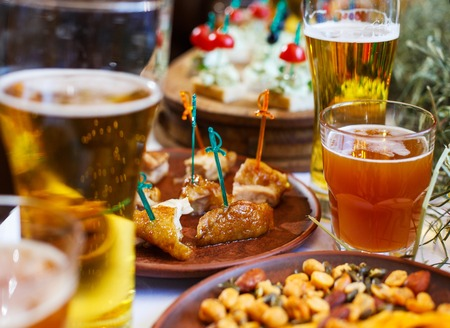 Delicious snacks for beer. Hot fragrant chicken on a clay plate between cups of beer. Stock Photo