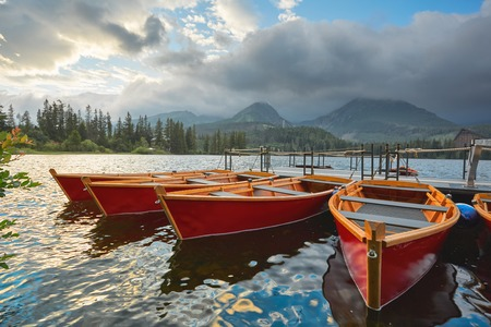 Red boats on a mountain lake against the background of a cloudy sky. Stock Photo