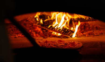 Professional pizza oven. A good fire burns in the oven. Pizza on the wooden shovel in the oven.