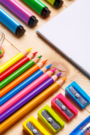 Bright crayons, markers and sharpeners along with a notebook on the table