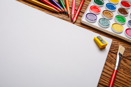 Bright paints along with the pencils and the album Stock Photo