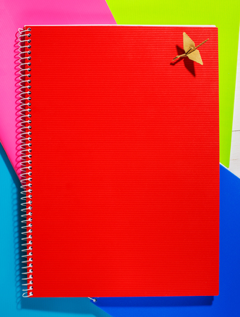 Back to school. The red notebook is on colored paper Stock Photo
