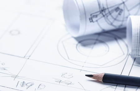 Pencil and rolls with a drawing against the background of drawing details