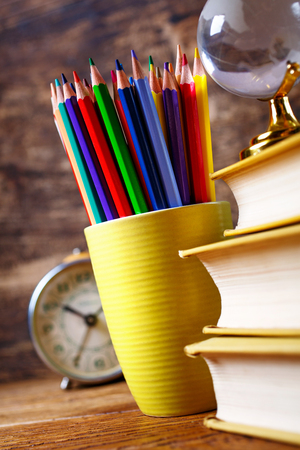 Colored pencils in a glass next to books and watche. Concept of education or back to school. On a wooden background