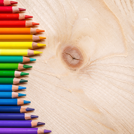Pencils in rainbow color wave laid on wooden background. Top view, flat lay. copyspace Imagens