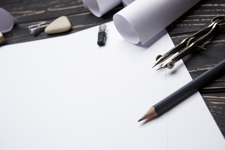 Sit at the table and create your drawing. office workspace with blank paper, pencils and various drawing tools. selective focus