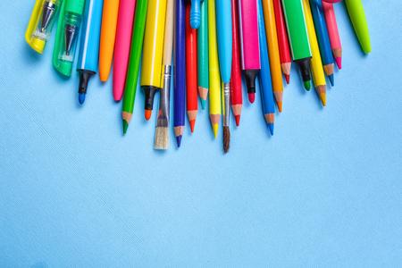 Farbstifte, Bleistifte, Marker und andere Gegenstände liegen auf hellblauem Hintergrund. Konzept der Bildung oder zurück zur Schule. Ansicht von oben, flach. Exemplar