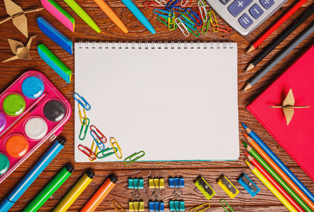 Bright stationery is laid out around the notebook. On a wooden background. Top view, flat lay. copyspace