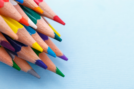 A group of bright wooden pencils lying on a blue background. Drawing supplies: assorted color pencils. copyspace