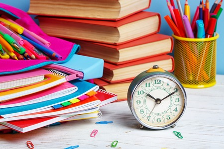 Composition lined with colorful school stationery. At 10 oclock hour is time to study. Group of school supplies and books on wooden table Stock Photo