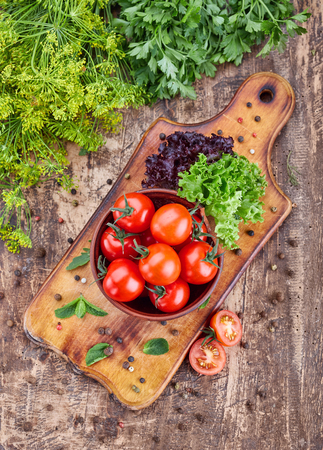A plate of fragrant tomatoes on a wooden board with mint. Top view