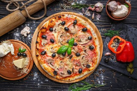 Exquisite pizza with ham, mushrooms and olives. Poster for Restaurants or pizzerias. Pizza on a black wooden background among spices