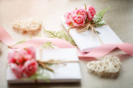 Couple of gift boxes wrapped with simple white craft paper and decorated with bouquet of roses and green bunch. Satin pink ribbon and wooden heart. Selective focus