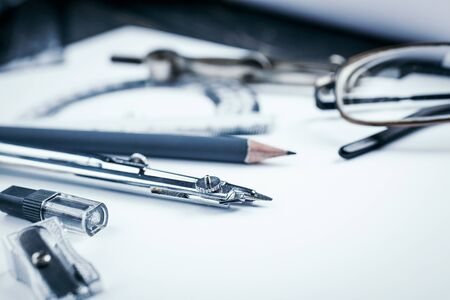 Work with the drawing. On the desk are tools for creating drawings. Desktop for the architect. selective focus Stock Photo