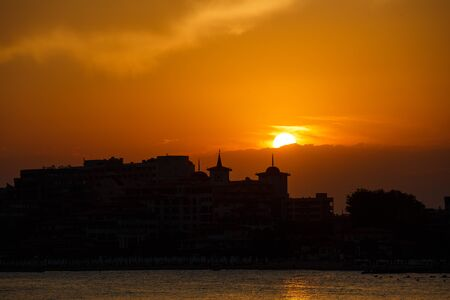 Golden sunset on the beach. Silhouette of the city. Beautiful architecort by the sea on the background of the sunset. Calm and travel concept. Sveti Vlas, Bulgaria. Sunny Beach Zdjęcie Seryjne