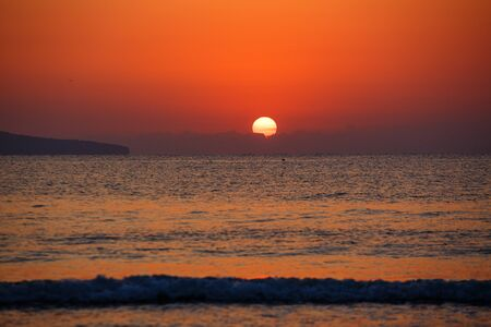 Beautiful sunset landscape at black sea and orange sky above it with awesome sun golden reflection on calm waves. Amazing summer sunset view on the beach.