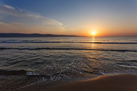 Sunset. Summer landscape. Peaceful evening on the shore of the ocean.