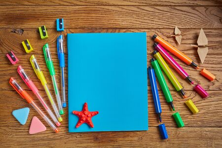 Back to School. Bright office supplies near a notebook with a star. on a wooden background. Top view, flat lay