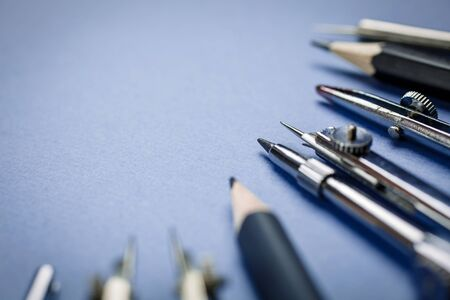 Compasses next to the pencils are laid out on a blue background Imagens - 128807290