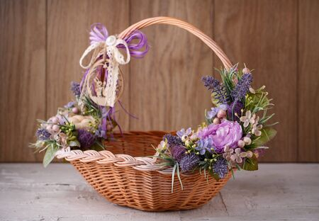 Beautiful decorative basket with flowers to celebrate Easter on a wooden background Zdjęcie Seryjne