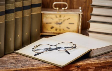 Open books ready for reading on the desk. An open book with glasses along with an ancient clock .
