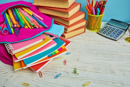 On the table is a composition from school stationery. School background. School and office supplies frame