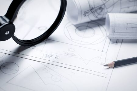 Magnifier for work with small details of the engineering drawing. architectural background with rolls of technical drawings and blueprints. selective focus Banco de Imagens