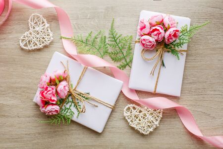 Eco style gift wrapping. Composition with gift boxes decorated with green branch, rose, wooden hearts and satin pink ribbon. Top view, flat lay