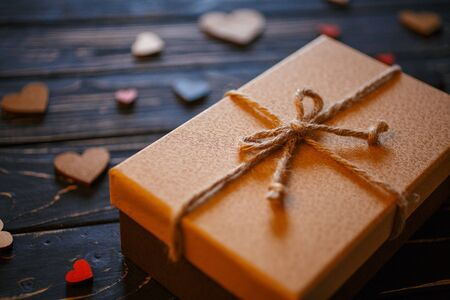 Brown gift boxes on wooden background with a bow of a simple rope closeup. Love, celebration and gift concept. Zdjęcie Seryjne